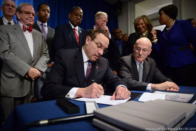 Mayor Gray signs the Minimum Wage Amendment Act of 2013 while Phil makes sure he crosses his T's and dots his I's.  Photo courtesy of Lateef Mangum.
