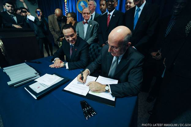 Phil signing the Minimum Wage Amendment Act of 2013.  Yes, he does get to go first!  Photo courtesy of Lateef Mangum.